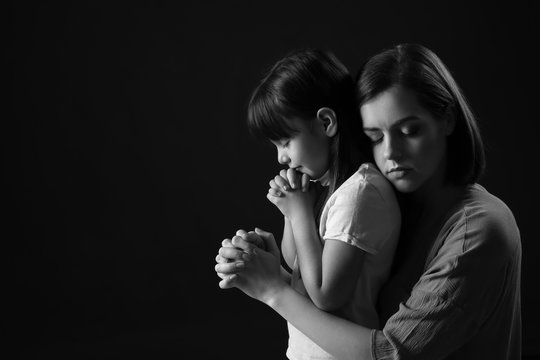 Praying mother and daughter on dark background