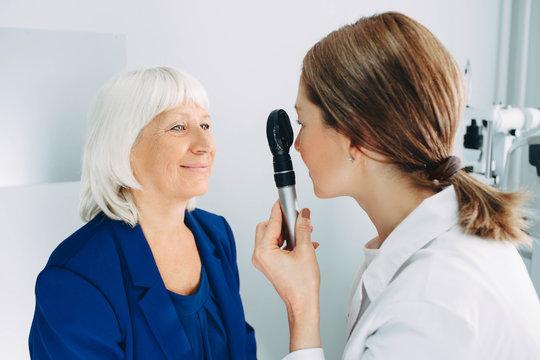 Senior woman visiting optician, eye exam at clinic