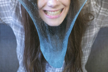 Woman is stretching a blue slime and playing. Close-up woman's smile.