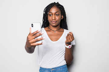 Young African American woman taking a selfie isolated on gray background