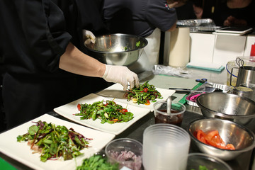 Chef preparing fresh salad with grilled fish for serving in kitchen