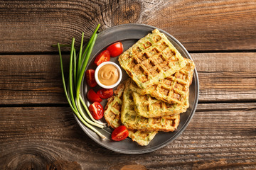 Metal tray with tasty squash waffles and sauce on wooden table