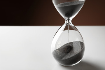 Crystal hourglass with falling sand on white table. Deadline concept