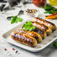 Grilled sausages with sauce vegetables and herbs. Selective focus, space for text.