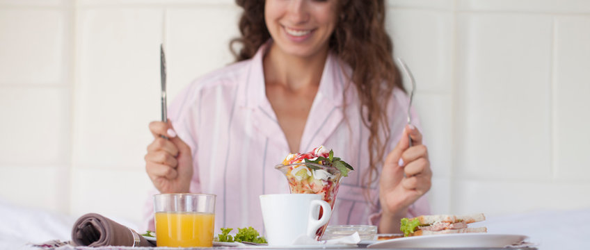 Smiling happy woman having a relaxing healthy breakfast at home.