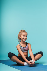 Cheerful young sports girl sitting on a fitness mat