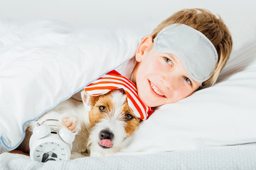 Сunning boy and his dog jack russel terrer stick out waking in masks, alarm clock under blanket in bed at home. School age child and dog at home, winter day, cozy lifestyle concept.