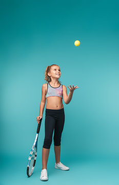 Cheerful young sports girl playing tennis