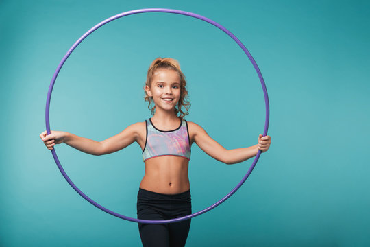 Cheerful little sports girl doing exercises with a hula hoop