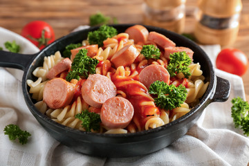 Delicious pasta with sausage and sauce on pan