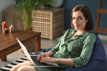 Young woman with laptop sitting on beanbag chair at home