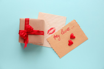 Valentine's Day card with gift box on color background