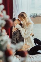 Sexy young woman and handsome man are sitting on bed in sweaters and hugging.Young pretty couple celebrating Christmas together at home near Christmas tree.