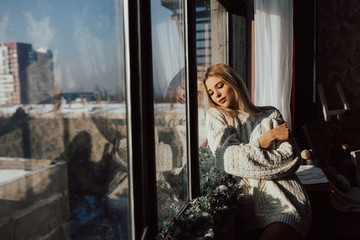 Sensual attractive blond woman dreaming near the window dressed a white sweater. Woman in the morning.