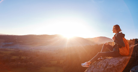 woman sits on edge of cliff against background of sunrise