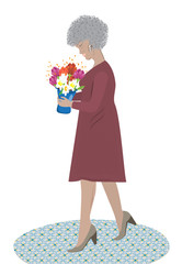 An elderly woman with gray hair holds a vase with a bouquet of flowers