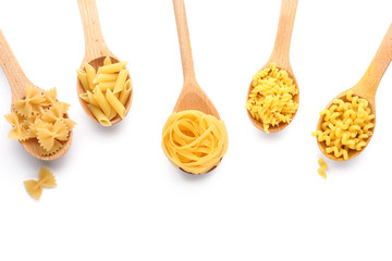 Wooden spoons with various uncooked pasta on white background