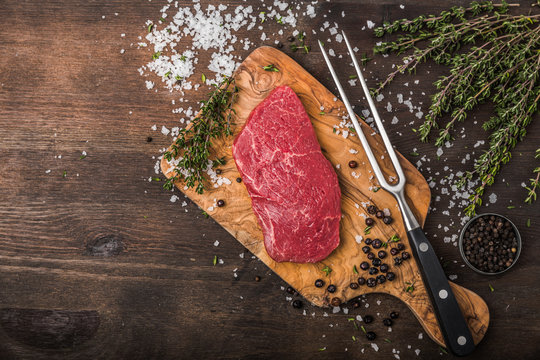 delicious raw beef sliced on a wooden background with herbs