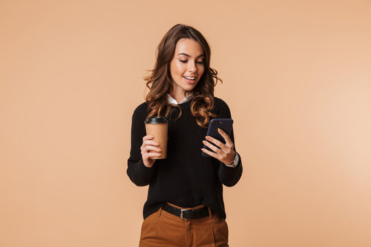 Smiling young woman wearing sweater standing