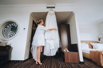 Beautiful bride looks at a dress. Wedding interior. Charges the bride at the hotel. Wedding photography.