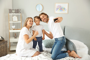 Happy family taking selfie in bedroom