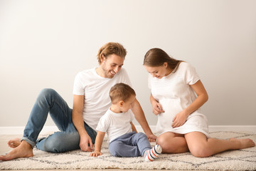 Portrait of happy family on carpet near white wall