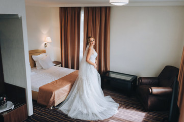 A lovely bride with a long dress is standing in a beautiful room and smiling. Wedding interior. Charges the bride at the hotel. Wedding photography. Portrait of a beautiful bride.