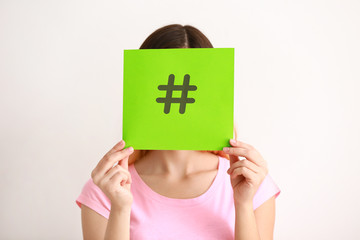 Woman holding sheet of paper with hashtag sign on white background