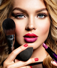 Beautiful woman holds cosmetic tools. Makeup.
