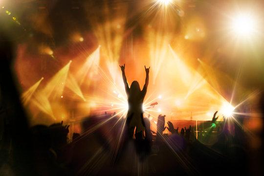 concert rock artiste musique musicien guitariste public ambiance main levée spot lumière scène
