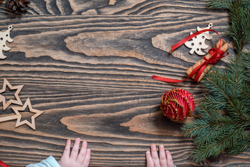 children's hands on a wooden background. Christmas Card. green tree, red balls, sweet lollipops. The child takes Christmas candy from the table. White snowflakes. Flat lay, top view. copy space