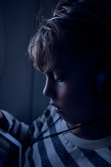 Cute boy watching film on tablet in plane