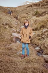 Cute boy standing on hill near brook