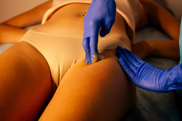Beautiful client and dermologist cosmetologist woman having a sugaring depilation bikini area beauty treatment in the spa salon
