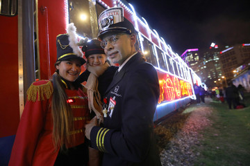 Workers of the tourist train 'La Sabana' decorated with Christmas lights, pose for a photo with a girl in Bogota