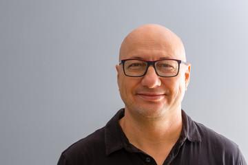 Portrait of smiling bold adult man