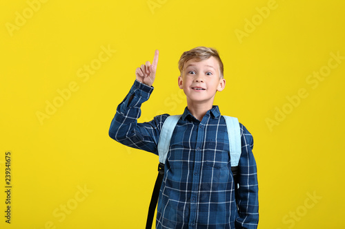 2413d34f24 Cute little schoolboy with backpack and raised index finger on color  background