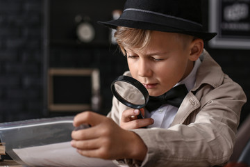 Cute little detective working with evidence at table