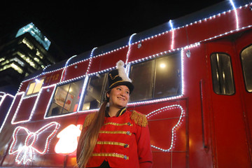 A worker of the tourist train 'La Sabana' decorated with Christmas lights, poses for a photo in Bogota