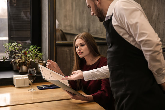 Young waiter showing woman a menu in restaurant