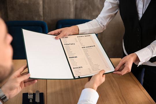 Young waitress showing man a menu in restaurant