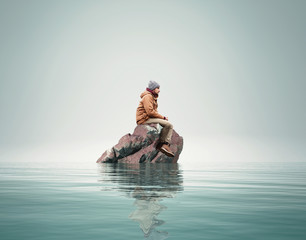 Man stands on a rock in the middle of a lake.
