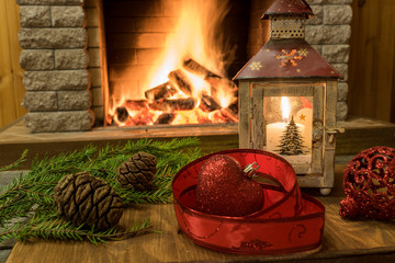 christmas lantern ,balls , red ribbon and cones , on old brown table, before cozy fireplace.