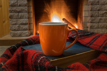 Cozy scene before fireplace with orange mug with tea, a book, wool scarf.
