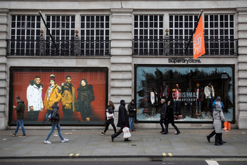Shoppers walk past a window display at a Superdry store on Regents Street in London