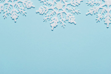 White glitter snowflake composition on a pastel blue background