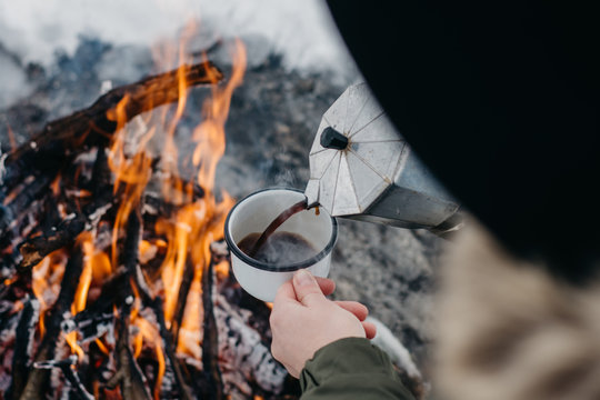 Traveling-woman  a  sits near camp fire an in winter time and pours itself hot coffee . Concept adventure active vacations outdoor. Winter camping