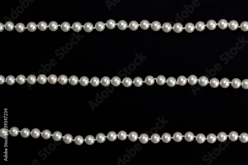 053dba19724a5d Rows of pearl necklace on the black background. Elegance and jewelry  concept. Top view, flat lay, copy space, card layout