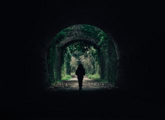 Chica en túnel de roca con un fondo natural verde, aire mágico y misterioso