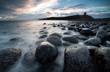 View at sunrise towards the ruin of Dunstanburgh Castle from the beach of basalt boulders known as The Rumble Churn at the southern end of Embleton Bay, Embleton, near Alnwick, Northumberland, England, United Kingdom, Europe